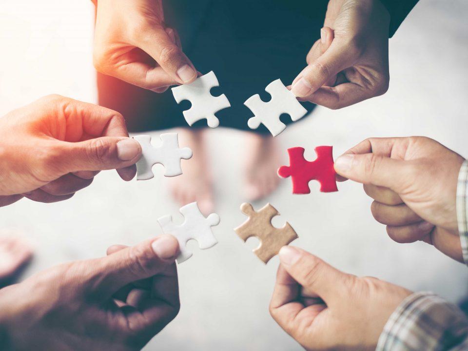 mains tenant une pièce de puzzle symbolisant l'esprit d'équipe